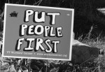 yard sign with Put People First printed on it; a hen in the grass behind the sign