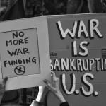 hands holding up signs saying No More War Funding and War is Bankrupting U.S.