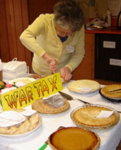 several dessert pies on a table with a sign that says WAR TAX above them. in the background, someone cutting a pie.