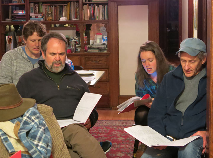 four people singing along from songbooks while seated