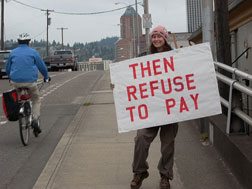 "woman on bridge holding sign that reads ""then refuse to pay"" as bicyclist goes by"