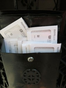 image of black mailbox with a dozen IRS envelopes sticking out the top