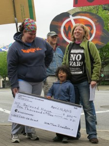 a child holds an oversized check made out to Beloved House from the Conscience and Military Tax Campaign