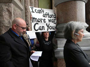 "woman holds sign reading ""I can't afford more war. Can you?"" as two button-down types walk by"