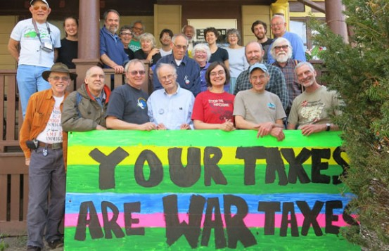 "Conference attendees posing behind a large sign that reads ""Your Taxes are War Taxes"""