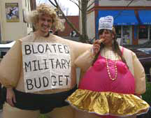 "two war tax resisters in ""fat suits"", one labeled ""Bloated Military Budget"""