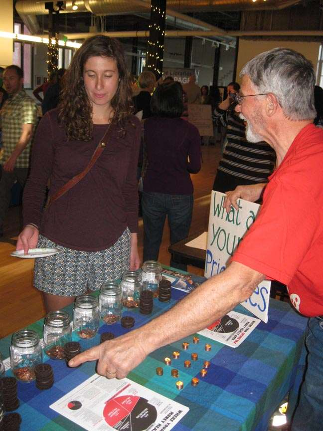 a man behind a penny poll table points at the jars while a woman holding a plate approaches