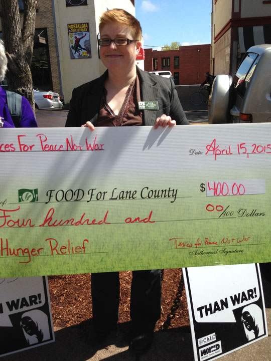 "woman holding oversized check made out for $400 from ""Taxes For Peace Not War"" to ""Food For Lane County"""""