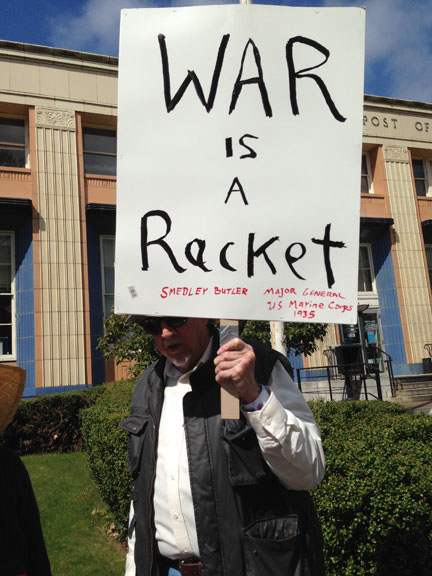 "Man holds picket sign reading ""War is a Racket"" (Smedley Butler)"