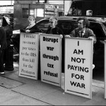 """protesters hold signs, for example: """"I Am Not Paying For War"""""""