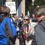 "Peg Morton stands in front of a camera talking at a Eugene Tax Day rally in 2015. A sign reading ""WAR IS A racket"" is held up behind her to the left."