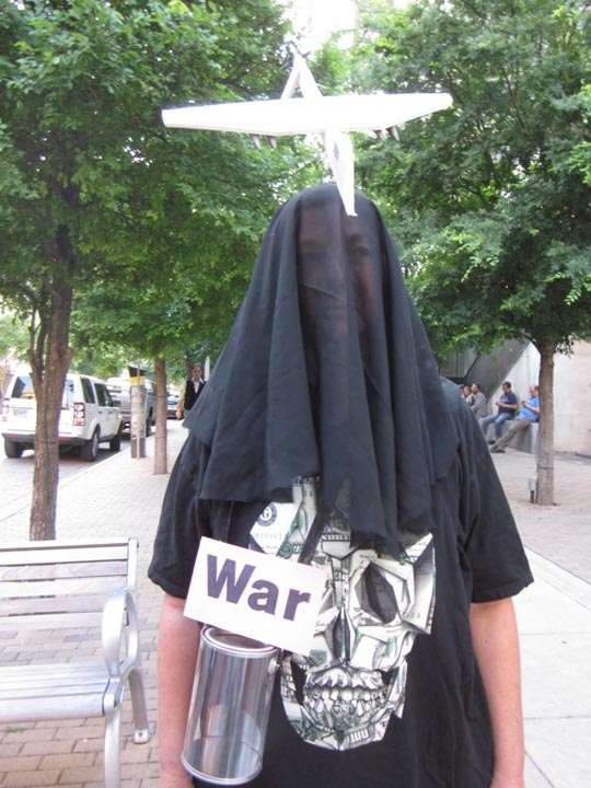 "Person shrouded in black with death-mask shirt, labeled ""War"""