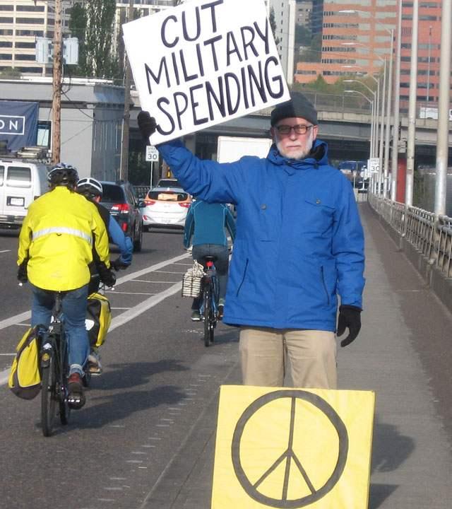 """John Grueshow on bridge holding sign reading """"Cut Military Spending"""""""
