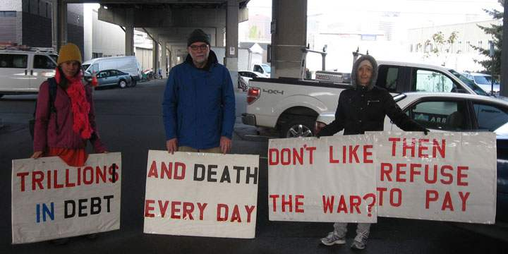 "Four people holding signs that have this message, printed sequentially: ""Trillions in debt"" / ""and death every day"" / ""don't like the war?"" / ""then refuse to pay"""