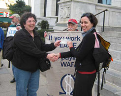 "two smiling women shake hands and exchange a check while a man holds a sign behind them that reads ""If you work for peace, stop paying for war"""