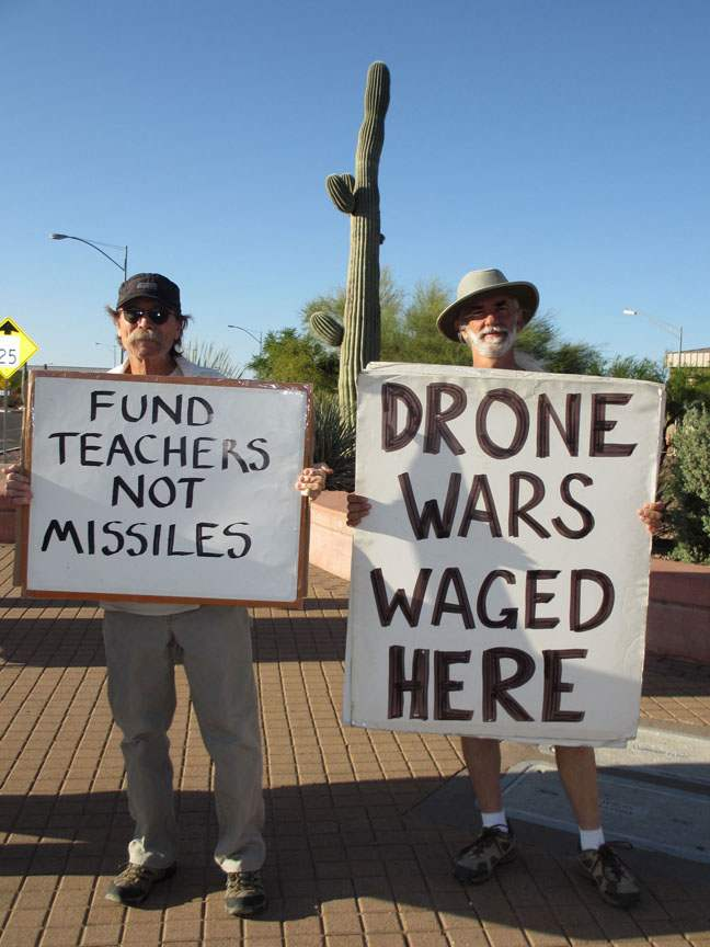 "Twi people hold protest signs: ""Fund Teachers, not Missile"" and ""Drone Wars Waged Here"""