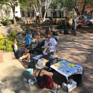 people mill about a literature table in a public plaza