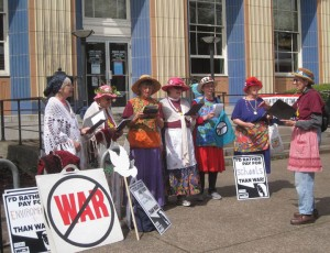 seven members of the Raging Grannies in costume singing outdoors with protest signs nearby