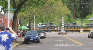 photo of train passing through intersection while carrying tracked vehicles