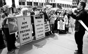 """war tax protesters with their signs, including """"I am not paying for war,"""" and """"War: Not with my money. I refuse to pay."""""""