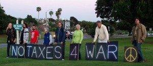 """eight people pose behind signs reading """"no taxes 4 war"""""""