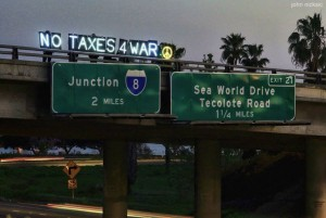 """the """"no taxes 4 war"""" illuminated letters visible on an interstate five highway overpass"""