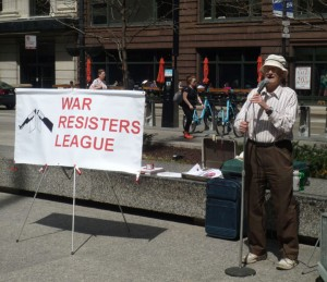 Brad Lyttle at the microphone with a War Resisters League sign nearby