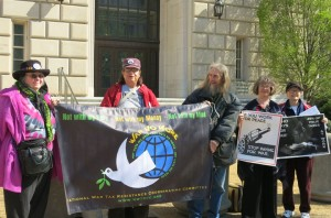 five activists hold banners and signs at the I.R.S. headquarters