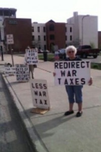 """people with protest signs including """"redirect war taxes,"""" """"less war tax,"""" and """"taxes for peace not war"""""""