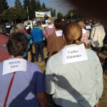Two people attending the rally wearing a piece of paper on their backs with the names of victims of the atomic bombings: Shoichi Sano and Yuriko Hatanaka. Other people in front of them are also wearing papers on their backs with victims' names printed on them.