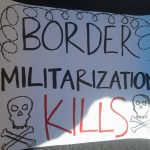 """white sign with skull and crossbones and barbed wire, saying in black and red text: """"BORDER MILITARIZATION KILLS"""""""