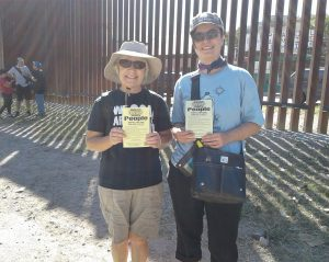 "Anne and Erica standing at the border with NWTRCC's ""Divest from war, invest in people"" flyers (Spanish text on the back!)"