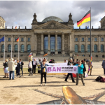 """A protest in front of the Reichstag - two people hold a banner reading """"BAN URANIUM WEAPONS"""" in front of a scattered group of about 40 people."""