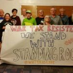 "A group of about 15 people standing with a paper banner reading ""War Tax Resisters: We Stand with Standing Rock #NoDAPL #waterislife"""