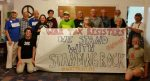 """A group of about 15 people standing with a paper banner reading """"War Tax Resisters: We Stand with Standing Rock #NoDAPL #waterislife"""""""