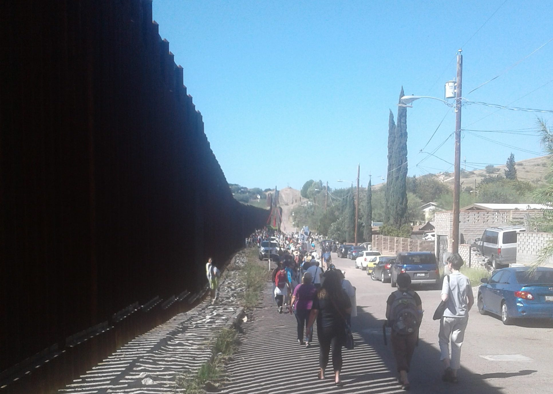 border fence stretches into the distance on the left, as SOAW border convergence attendees march alongside it