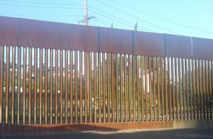 an image of the rusty brown border fence at Nogales, Sonora/Arizona, seen from the Mexican side