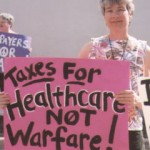 "woman holding pink sign with black text: ""Taxes For Healthcare NOT Warfare"""