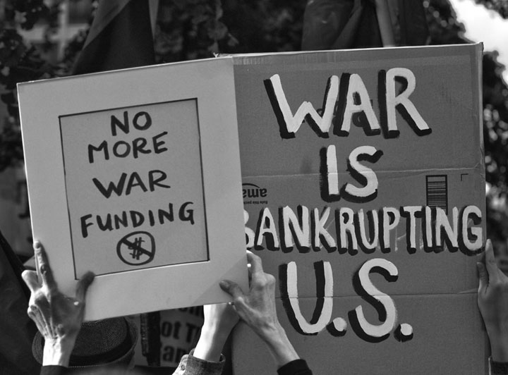 signs reading No More War Funding and War is Bankrupting U.S.