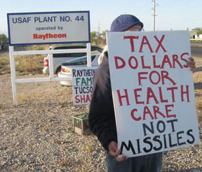 person holding sign saying Tax Dollars for Health Care Not Missiles