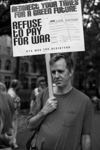 "Walter Goodman holding a sign on a stick: ""Redirect Your Taxes for a Green Future. Refuse to Pay for War."""