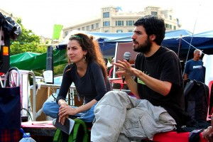 Enric Duran, seated, speaks into a microphone in his hand. Núria Güell, also seated, sits to his left. Tents in the background.