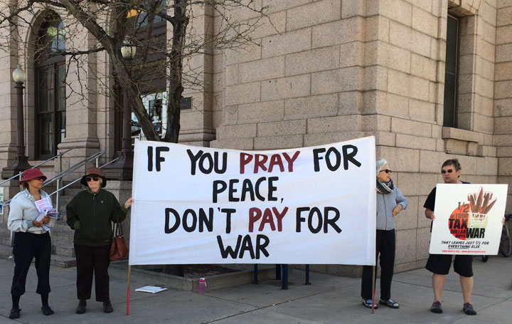 """Four people holding signs, banners, and leaflets. The large banner says IF YOU PRAY FOR PEACE, DON'T PAY FOR WAR. The smaller sign to the right says """"1/2 of your tax goes to war."""""""