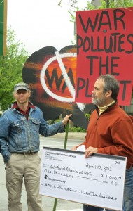 Bill and Jason with anti-war signs and a giant check of resisted war taxes