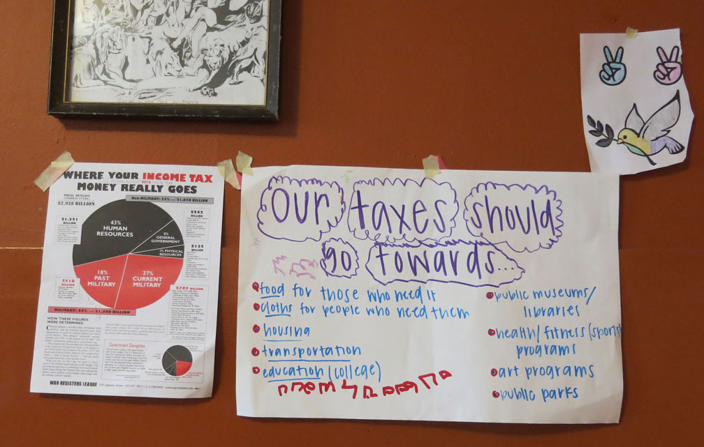 "War Resisters League pie chart alongside handwritten poster titled ""Our taxes should go toward,"" with a list of social programs including food, housing, and education"