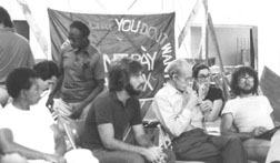 black and white photo of several attendees of the 1982 founding conference listening to a speaker