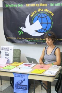 "Ari sits at the literature table with a ""War No More"" dove and earth banner behind her"