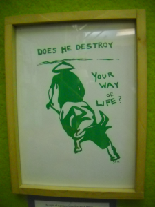 "poster with a painted image of farmer and bull with text, ""Does he destroy your way of life?"""