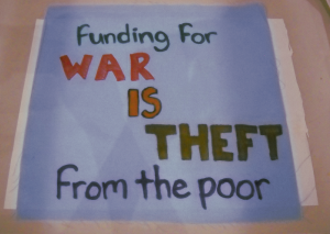 "fabric square with text ""funding for WAR IS THEFT from the poor"""