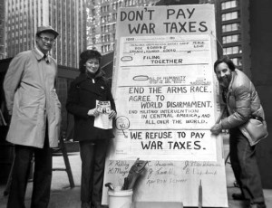 Brad Lyttle, Kathy Kelly, and Karl Meyer alongside a large sign reading 'Don't Pay War Taxes; End the arms race; agree to world disarmament; end military intervention in central America and all over the world. We refuse to pay war taxes.'